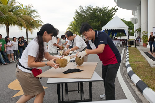 WOU Registrar Yeong Sik Kheong (foreground, right) and Dr Seah (centre) pry open the durians.