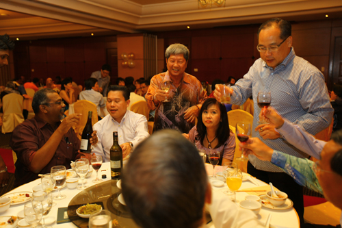 Prof Wong (centre, standing) and Dr Seah (right, in blue shirt)) raise their glasses.