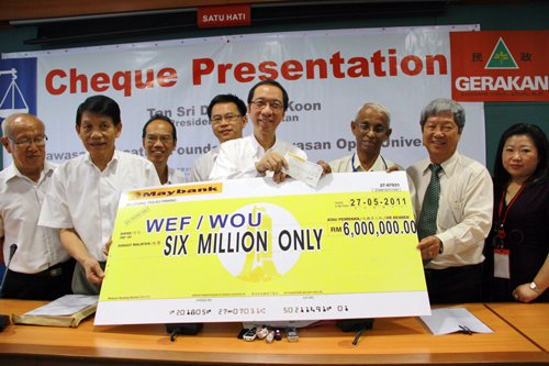 Tan Sri Dr Koh Tsu Koon (centre) presents the mock cheque to Tan Sri Emeritus Prof Gajaraj Dhanarajan (3rd from right) and Vice Chancellor Prof Wong Tat Meng (2nd from right).