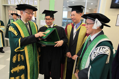 Dr Koh reads the inscription on Chan's (2nd from left) award.