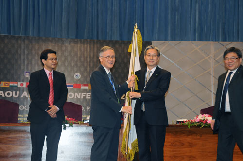 Prof Ho hands over the AAOU flag to Prof John Leong of OUHK.