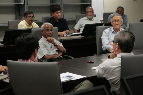 Prof Dhanarajan (facing, 2nd from left) gestures as he offers his input.