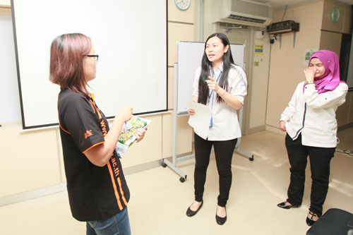 Loh and her colleague (right) entertain queries on investments.