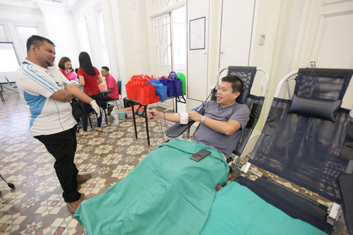 A Penang Hospital team member looks on as Chong donates blood.