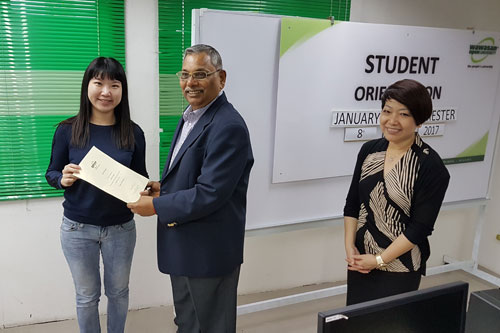 Prof Santhiram presents the Dean's List award to Lim Pui Shan. At right is Ipoh Regional Centre Director Ching Huey Ling.