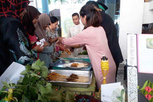 Staff buy satay from the Malay booth as Farid (centre, facing camera) looks on.