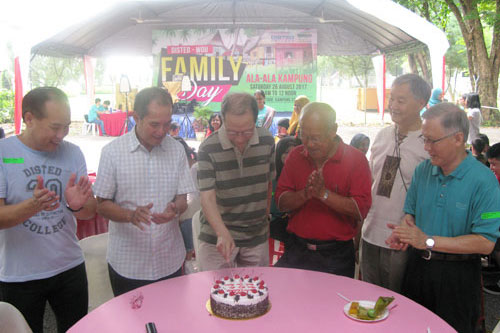 Dr Koh (centre) cuts his birthday cake as Dato' Seri Stephen Yeap (2nd from left) and others share in his joy.