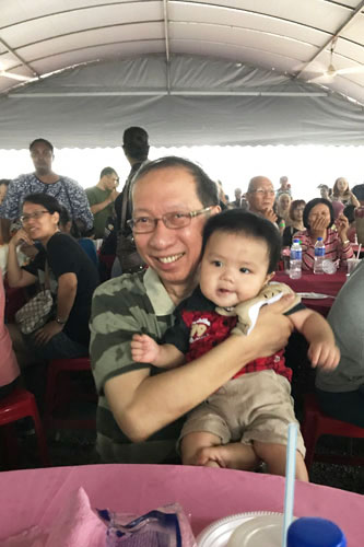 Adorable...Dr Koh cuddles 8-month-old Carl Lim, the son of Angelynne Soh of Wawasan Open University.