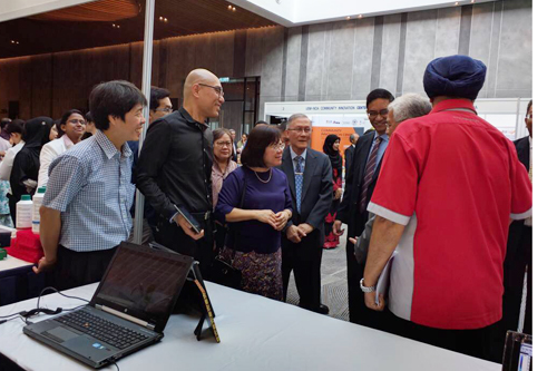 Dato' Seri Idris (partly hidden) visits the exhibition booths.