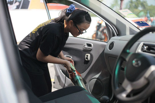 Vacuuming the inside of a car.