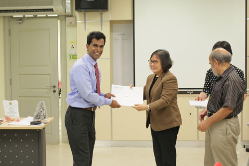 Prof Zoraini Wati Abas presents certificate of attendance to a participant.