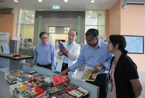Dr Koh (2nd from left) and Dr S. Nagarajan looking through the books.