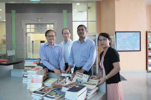 Leong (left) hands over the books to Dr Nagarajan and Chew (right) witnessed by Dr Koh.