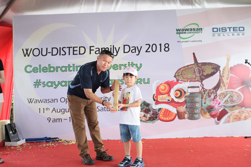 Regional Operations and MARCOM Director K H Chong presents a lucky draw prize- an aluminium baseball stick torchlight - to his son.