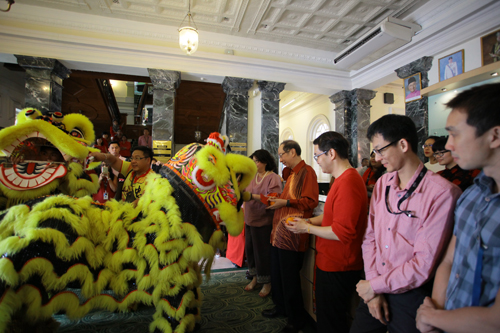 Tan Sri Dr Koh offers oranges to the 'lion'.