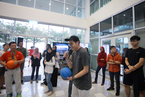 Holding the ball while introducing his team members to everyone present.