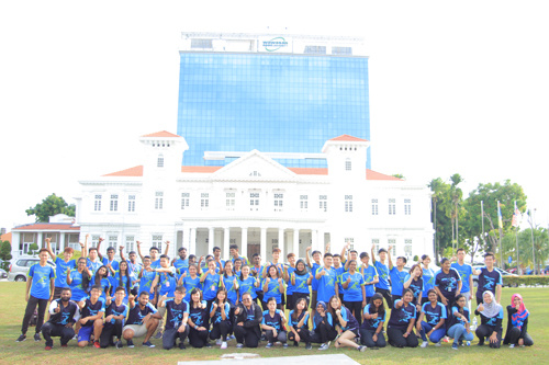 The participants pose in front the majestic campus building with the organsing committee and helpers.