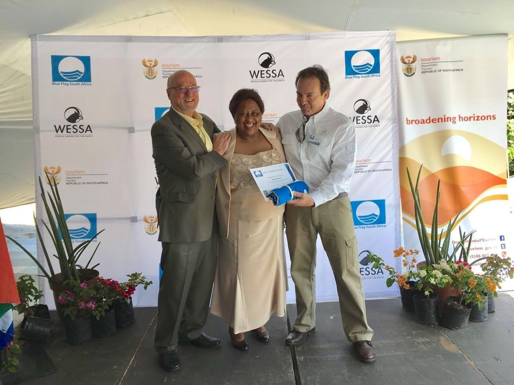 Figure 1: The mayor of Ray Nkonyeni Municipality, Nomusa Mqwebu (Centre) receiving the Blue Flag awards for all seven beaches within the municipality from the Minister of Tourism Dereck Hanekom (Left) and WESSA CEO Dr Thommie Burger (Right).