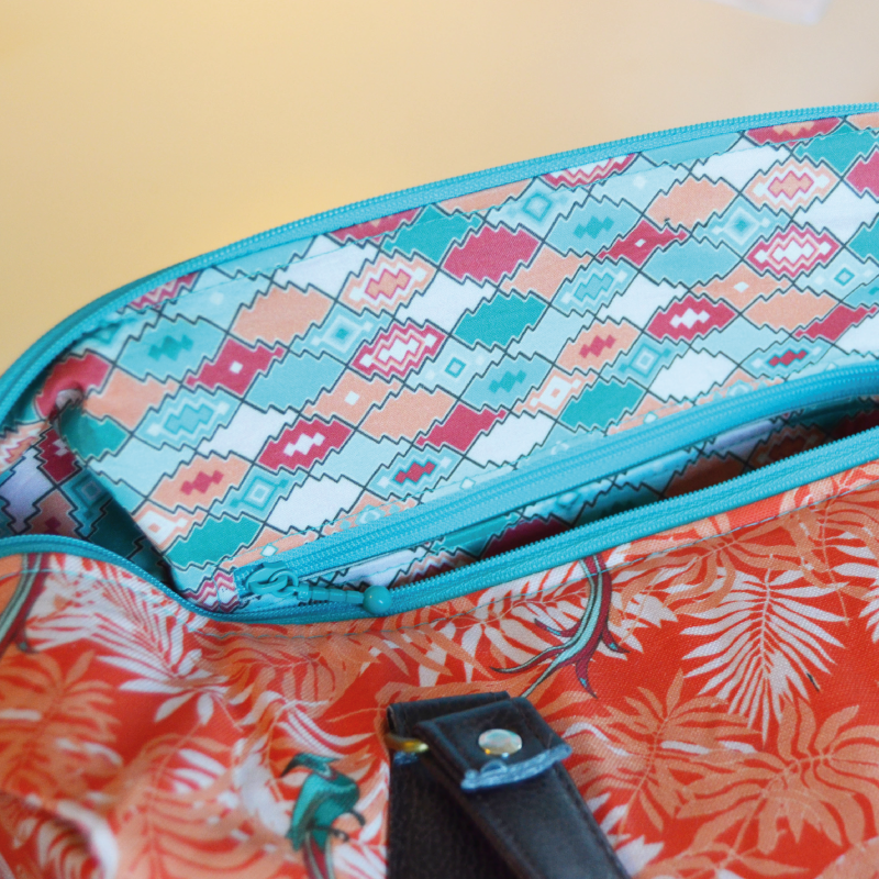 "The interior fabric with pattern design ""Sahara Rokoko"" is cotton. The roomy interior has a zippered side pocket."