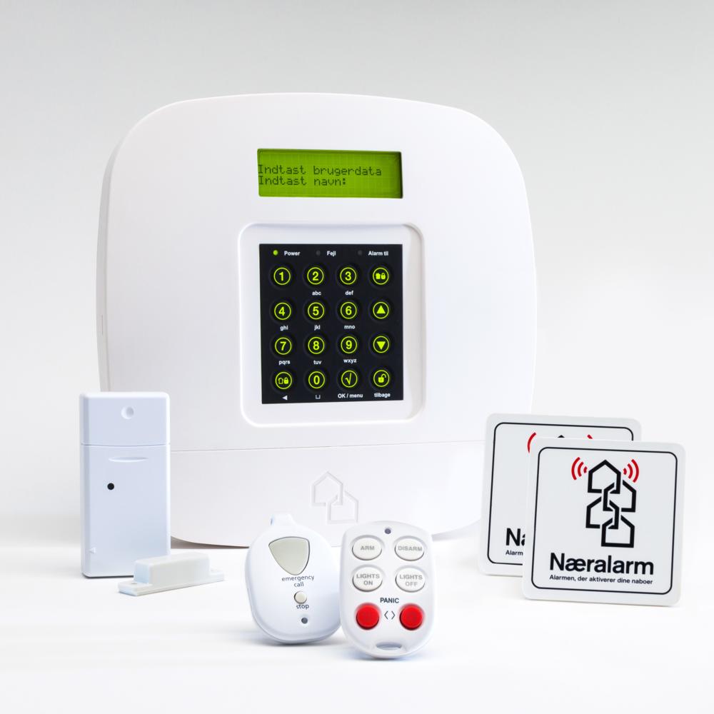 """Næralarms grundpakke  indeholder alarmcentral, alarmkontakt, fjernbetjening, nødknap og 2 alarmmærkater med teksten """" næralarm - alarmen, der aktiverer dine naboer """""""