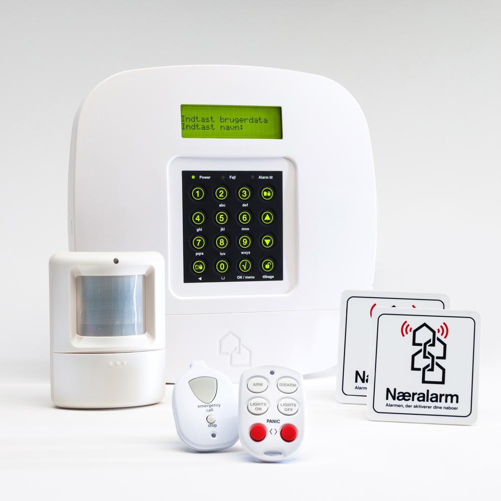 """Næralarms grundpakke med PIR  (Passive InfraRed) indeholder alarmcentral, bevægelsessensor, fjernbetjening, nødknap og 2 alarmmærkater med teksten """" næralarm - alarmen, der aktiverer dine naboer """""""