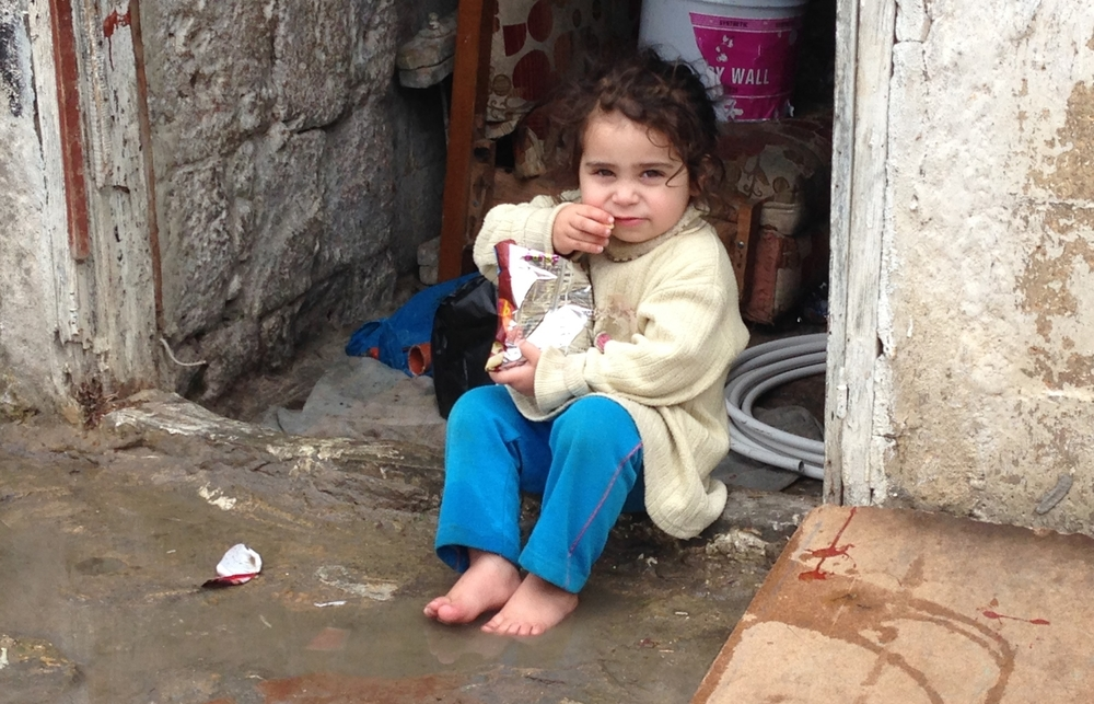 A tiny Syrian refugee sits in a rundown marketplace near the port of Tripoli in Lebanon. © Ruth Pollard 2014