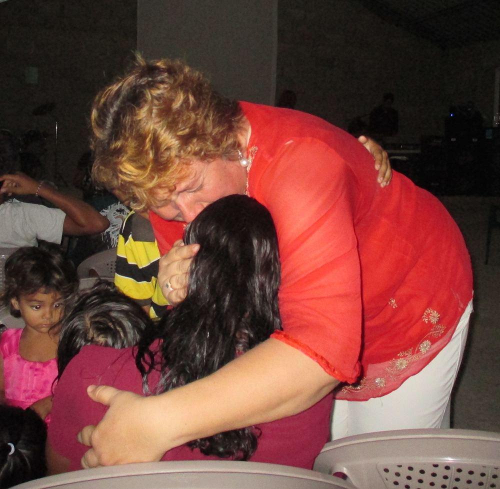 Pastora Eugenia praying with woman