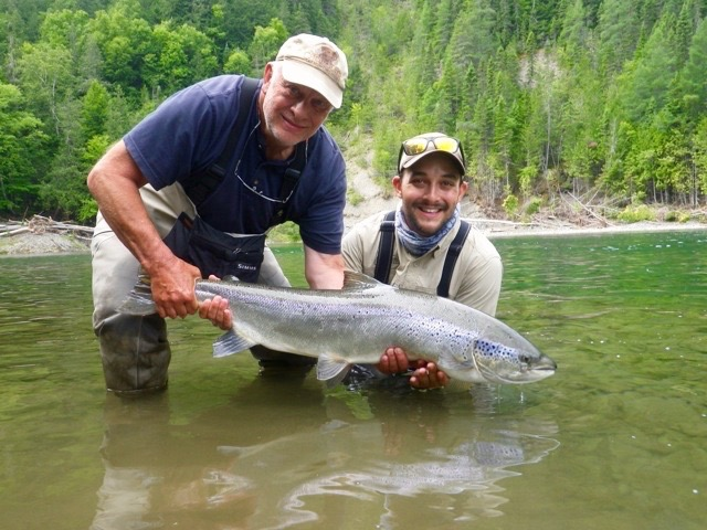 Long time Salmon Lodge guest, Claude Dagenais (left) releases a fine salmon on the Petite Cascapedia with Alex Mallais, the newest addition to our fine team of guides!