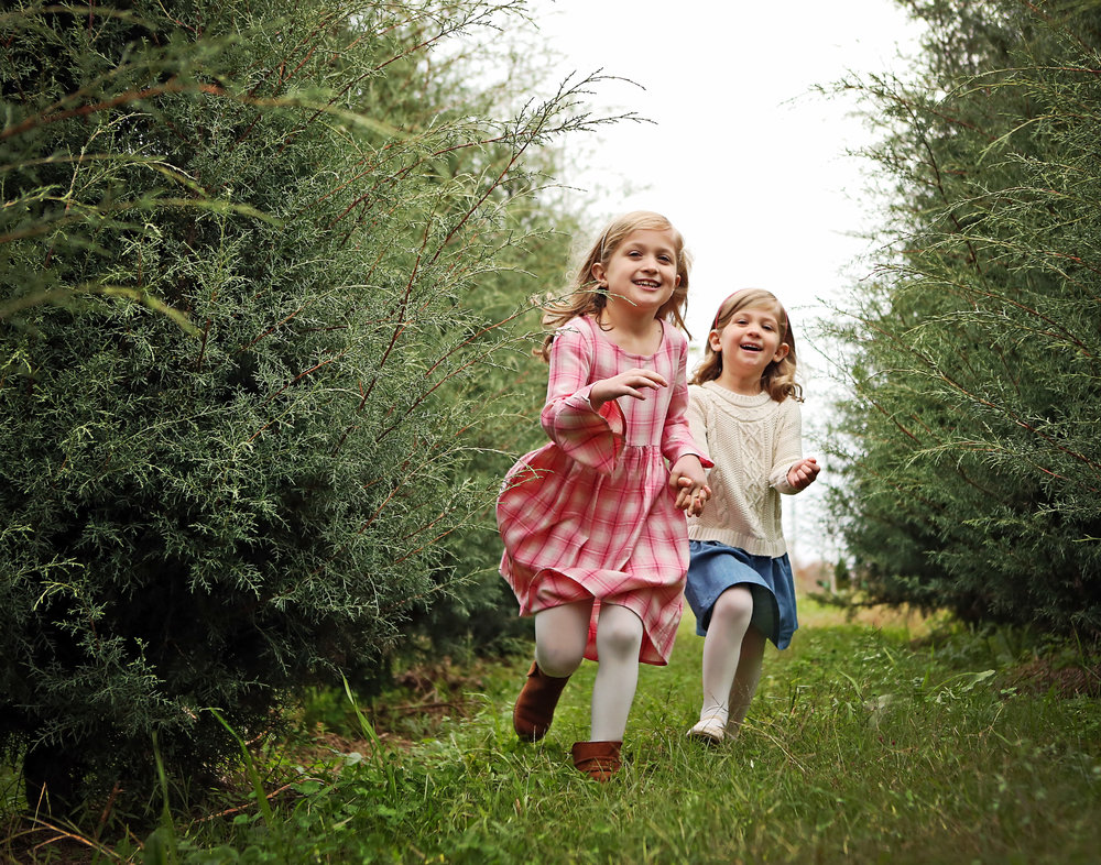 In a typical family portrait session, we will photograph both posed and candid portraits.  When it comes to photographing children, sometimes the best moments are when kids are just being kids.  We let these girls run through a Christmas tree farm in November and the result is a beautiful representation of sisterhood.