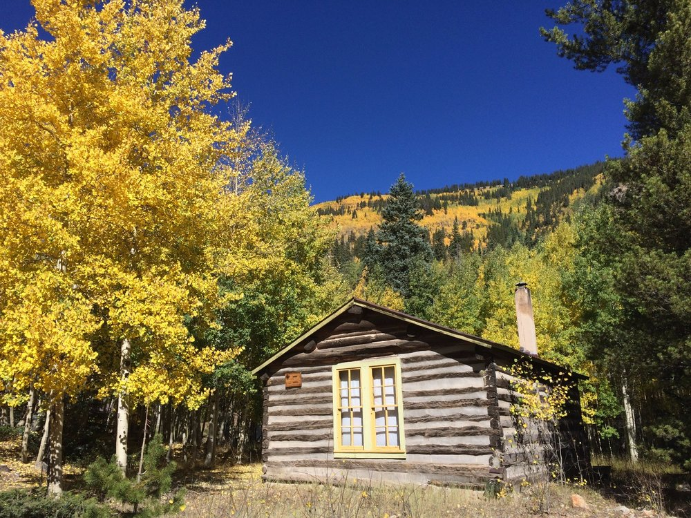 The yellow and green trim on this Cabin matches the surrounding aspen leaves