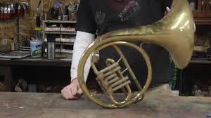 An iphone speaker made out of a busted french horn.