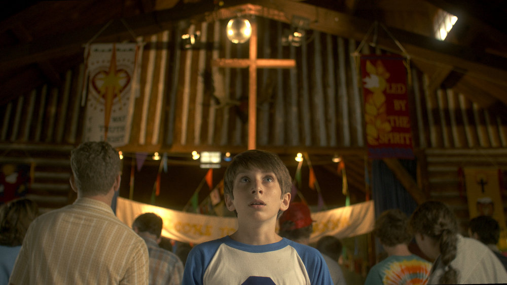 """Luke Klein stars in  Camp Manna as 15-year-old Ian Fletcher, a """"non-believer"""" shipped off to Camp Manna, a backwoods Christian summer camp run by the eccentric Vietnam vet Jack """"Cujo"""" Parrish (Gary Busey). / Photo courtesy Camp Manna LLC."""