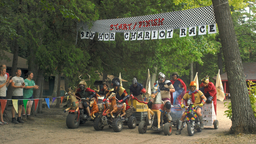 The God Games in  Camp Manna  include a Last Supper Pie-Eating Contest, a David-and-Goliath Stone Throwing Competition, the Ben Hur Chariot Race (above), and more. /  Photo courtesy Camp Manna LLC.