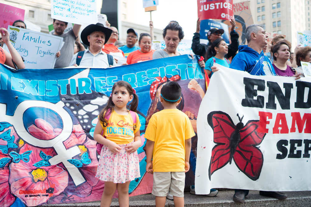 Children stand in front of protesters at the Families Belong Together demonstration.