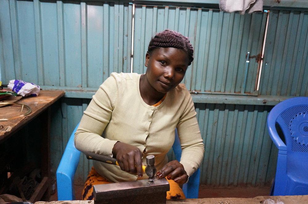 Sara at Kibera Hammering - artisan face.JPG