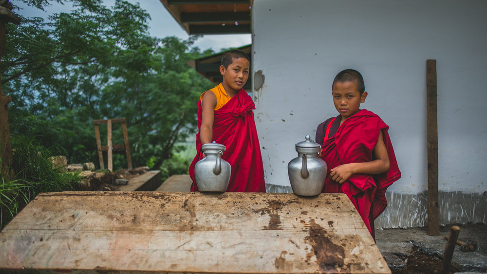 two Monks in The Kingdom of Bhutan. More than 30% of the population have committed their lives to being Monks. Living in quiet contemplation and prayer everyday with just the few friends around them who have also committed their lives to their faith.