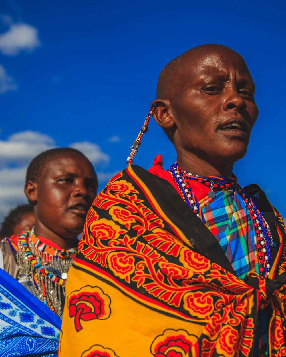 A mother, a leader, a Maasai Warrior leads a celebration with her fellow community mothers in honor of their daughters graduating high school and being the first women in the community to receive a high school education.