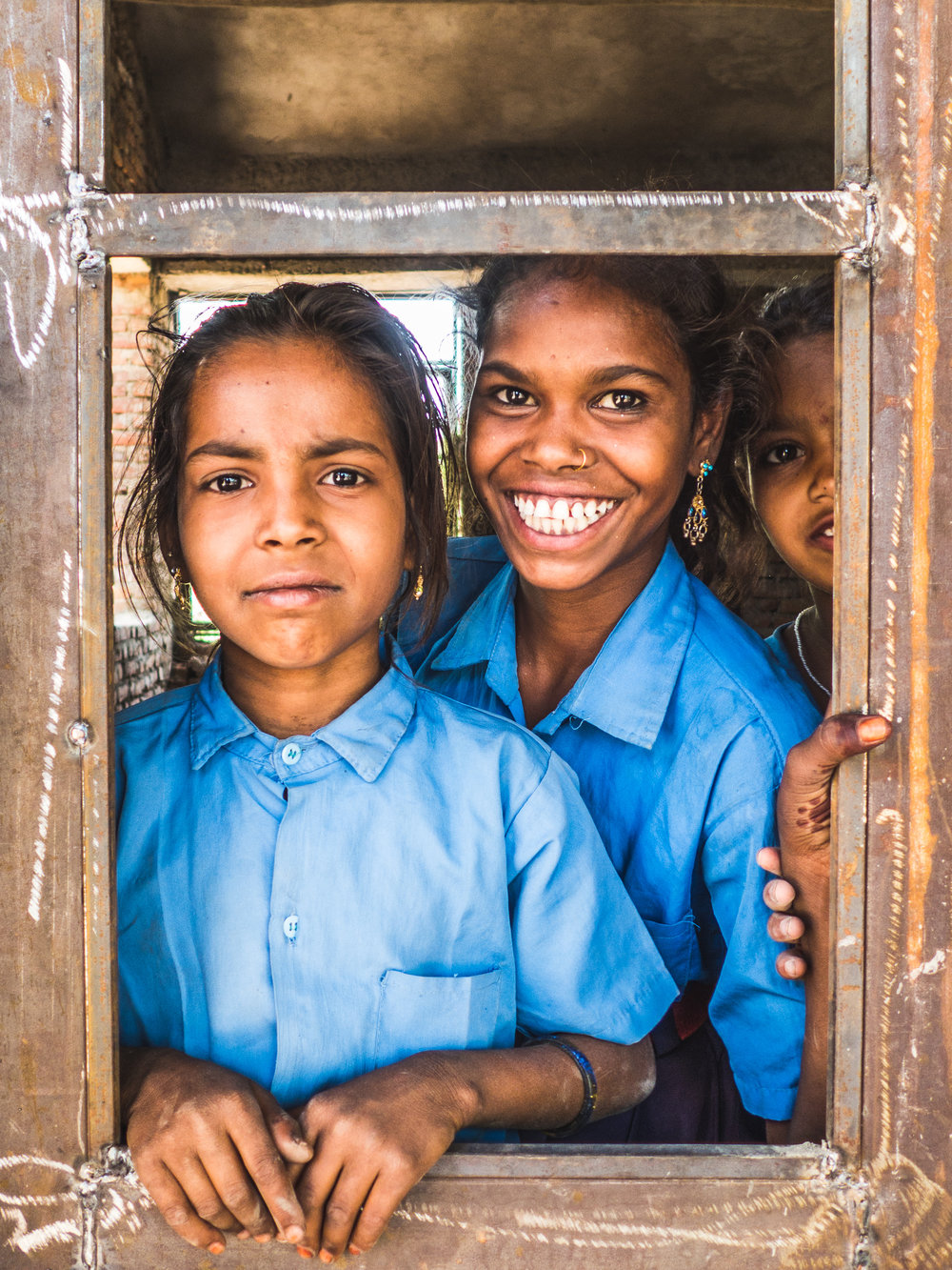 students in rural Rajasthan India standing by watching their community come together to help build a new school to expand the learning opportunities of girls in the community.