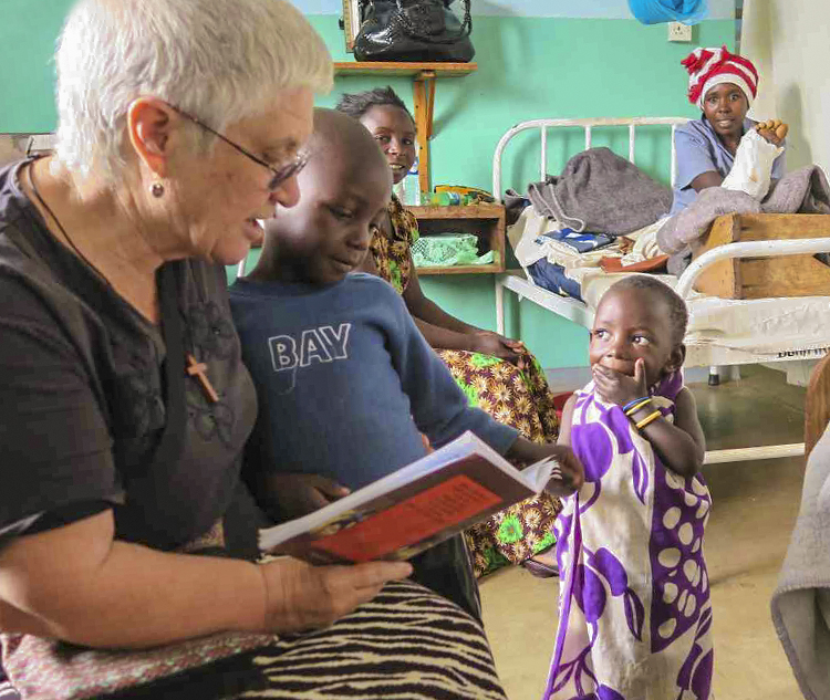 Jenny Bennett reading a book to patients at Murgwanza Hospital.