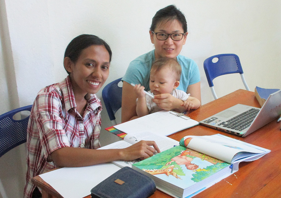Sandra (L) and Grace Adams (with Micah) translating The Big Picture Story Bible.