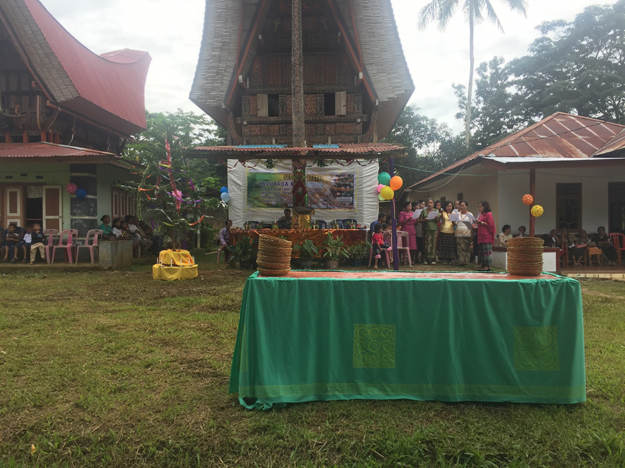A Christmas celebration in Toraja, Indonesia, with a group performing a choral item on the right of the ancestral house in the centre.