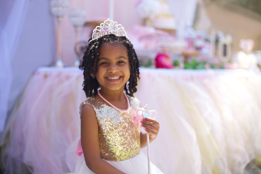 A rental collection with an elaborate ensemble of pink tutu centerpieces, white chiavari chairs, glittery runners, pink and white flowers, and sparkling tiaras that will dazzle even a Queen!