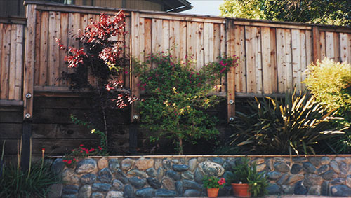 39_los ranchitos board on board fence with wood retaining wall and rock retaining wall.jpg