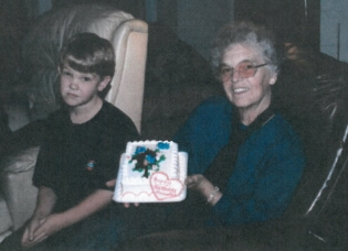 Pictured: T  he author's brother and grandma, with a safe, store-bought cake. T  he fact that we have no pictures of   her in the kitchen helps prove the point that she was not   immortalized there.