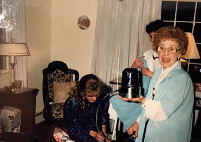 Marie La France in 1990 wearing her much loved Kmart blue smock. She is actually holding a Kmart flashing blue-light special lamp. The picture was taken during the author's sister's surprise 30th birthday party. She is laughing so hard she's doubled over.