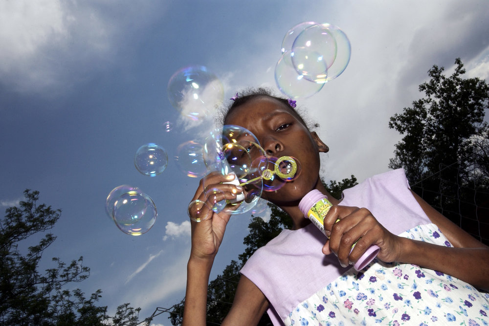 Nomalizo blowing bubbles, Sunflower Children's Hospice, Bloemfontein.