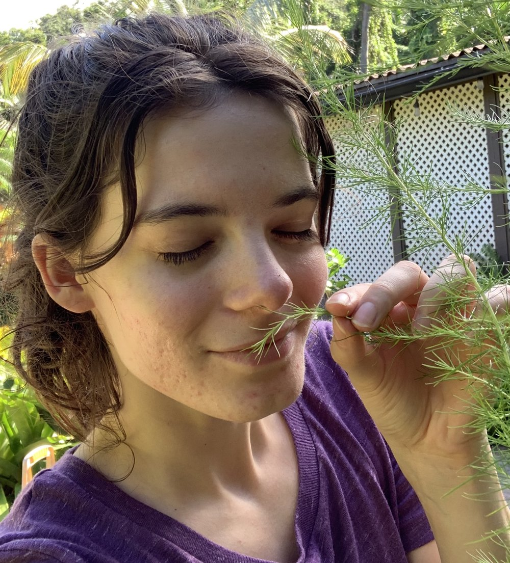 Volunteer (intern) Grace smelling the fresh herbs to decide how to season her dinner.