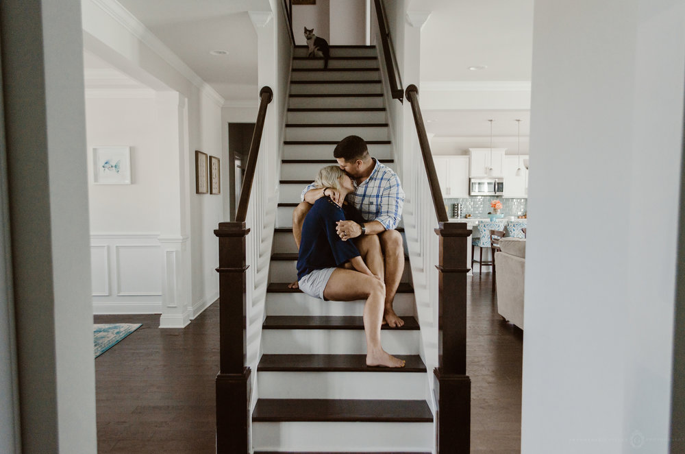 intimate couples session portait snuggles cuddling on stairs in home wilmington nc