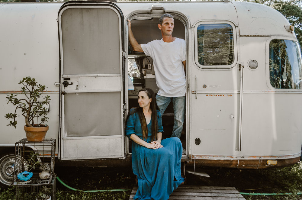 intimate couples photography session in vintage argosy airstream with blue and teal decor in wilmington nc wearing blue bohemian laced back maxi dress