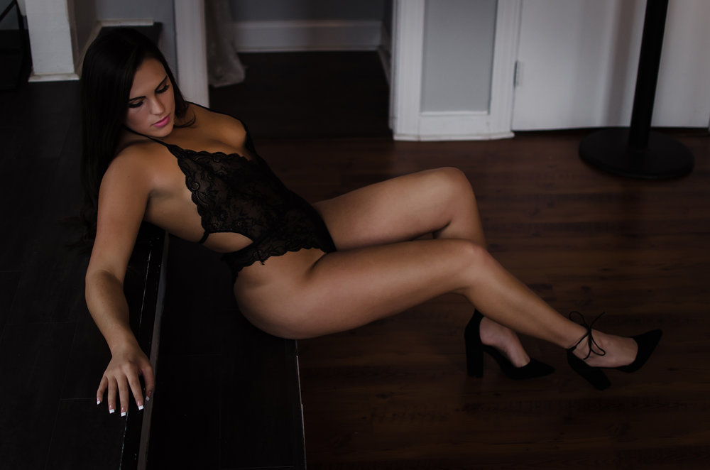 NC boudoir photography experience in belle vue wilmington venue with black lace bodysuit by Victoria Secret by Amandamarie Gillen Photography Wilmington NC photographer sitting on stairs and showing legs pose